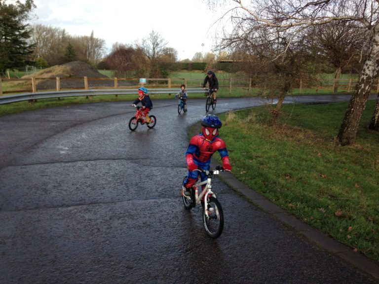 Child in Spiderman outfit cycling